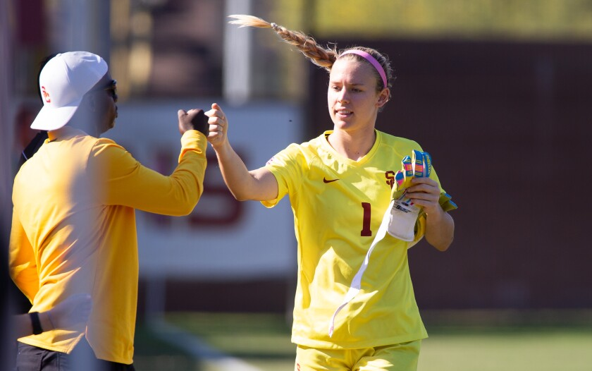 USC goalkeeper Kaylie Collins is congratulated by a coach.