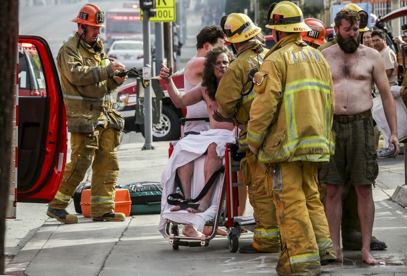 Firefighters tend to residents of a house that caught fire Saturday morning in Echo Park. One person was killed in the fire and several others were injured.