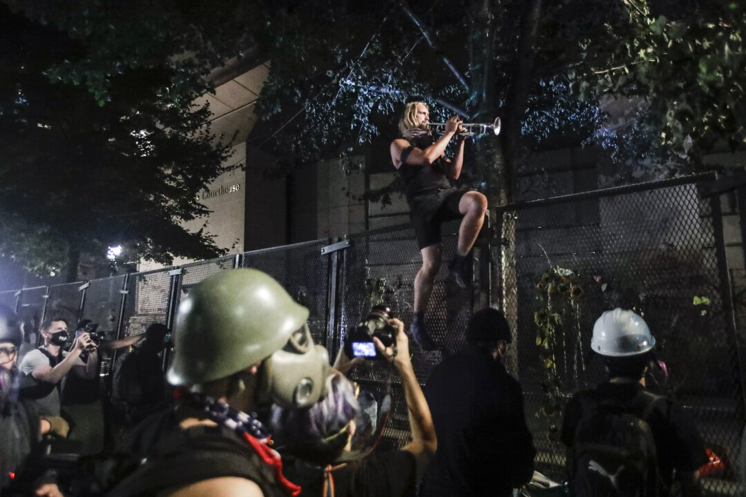 A demonstrator plays a trumpet from atop a steel fence during a Black Lives Matter protest in Portland, Ore.