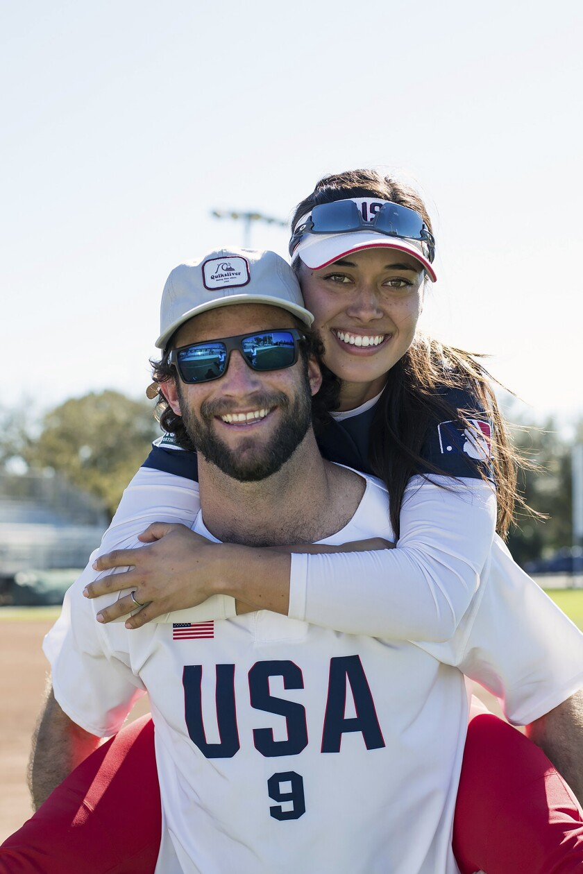 In this photo provided by USA Softball, Jake and Janie Reed pose for a photo in Clearwater, Fla., in February 2020. Getting ready to reach the height of softball and make her Olympic debut for the United States, Janie Reed was on a training field at Marine Corps Air Station Iwakuni, in Western Japan. Across the Pacific Ocean, 7,452 miles away, another important family first was unfolding in Miami: husband Jake Reed was about to walk onto a major league mound for the first time. (Jade Hewitt/Courtesy of USA Softball)