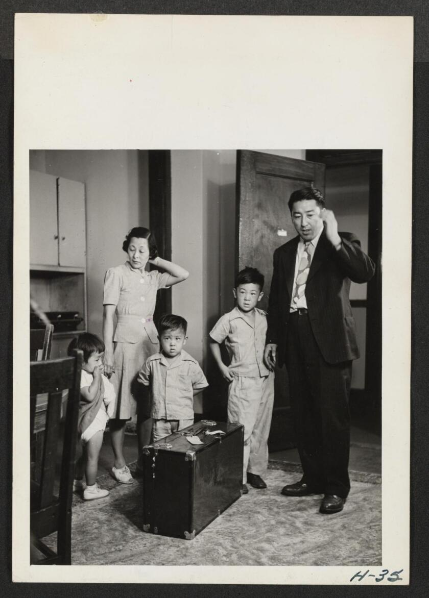 A black-and-white photo of two parents and three small children and a suitcase