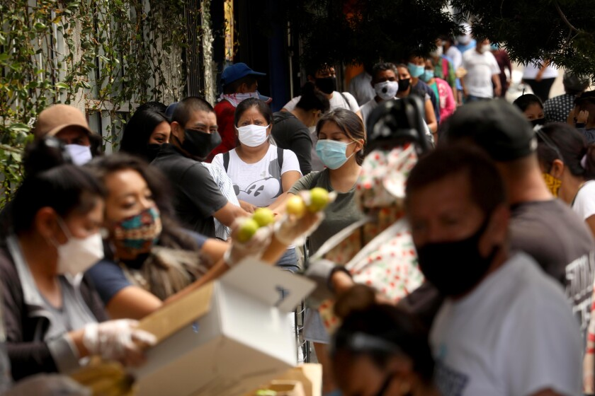 People struggling amid the pandemic wait in line in Koreatown on Wednesday to receive bags of food prepared by Homies Unidos.
