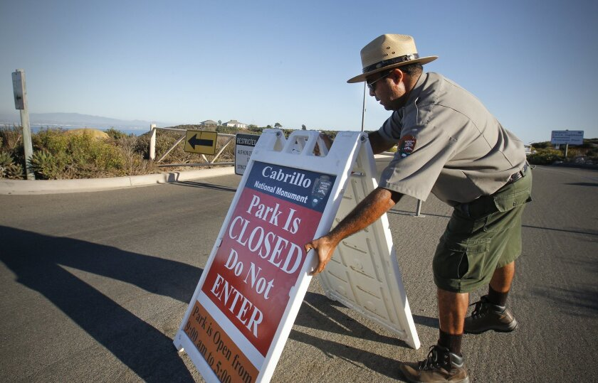 At 5:00 p.m., Daniel Martinez, National Parks Service ranger at the Cabrillo National Monument in Point Loma puts out the closed sign at the entrance to the monument, not knowing if the monument will open Tuesday, because of the looming shutdown of much of the federal government.