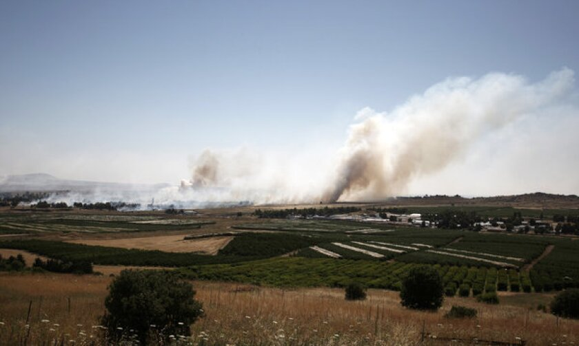 A picture taken from the Israeli side of the cease-fire line with Syria shows smoke billowing during clashes between Syrian rebels and forces loyal to the government.