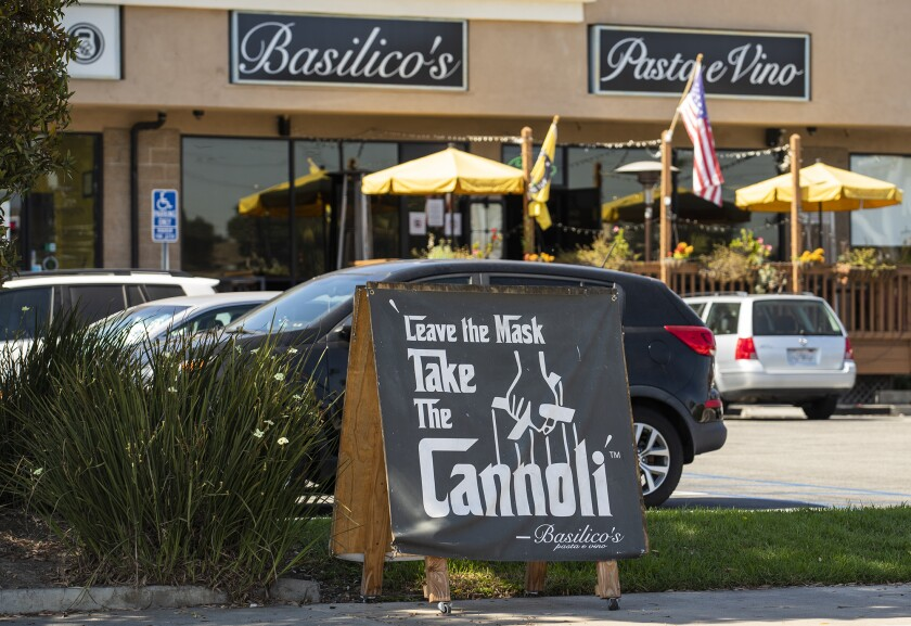 """A sign reading """"Leave the mask, take the cannoli"""" sits outside Basilico's in Huntington Beach."""