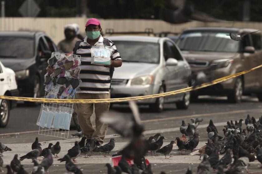 Un vendedor ofrece mascarillas en la plaza Gerardo Barrios de San Salvador, El Salvador, el viernes 7 de agosto de 2020, durante la pandemia del nuevo coronavirus. (AP Foto/Salvador Melendez)