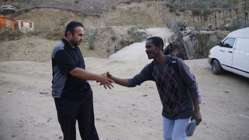 The Rev. Gustavo Banda, pastor at Templo Embajadores de Jesus, left, greets a Haitian migrant. The church offers housing to more than 60 Haitians.