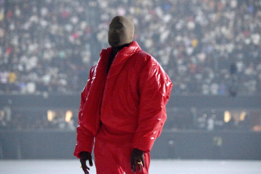 A man wearing a red coat and pants and a mask over his face