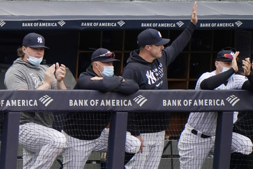 New York Yankees outfielder Jay Bruce, third from left, waves from the dugout as injured first baseman Luke Voit, left, applauds, while outfielder Brett Gardner rests on the railing as the Yankees announced Bruce's retirement from baseball during the seventh inning of the Yankees loss to the Tampa Bay Rays in a baseball game, Sunday, April 18, 2021, at Yankee Stadium in New York. (AP Photo/Kathy Willens)