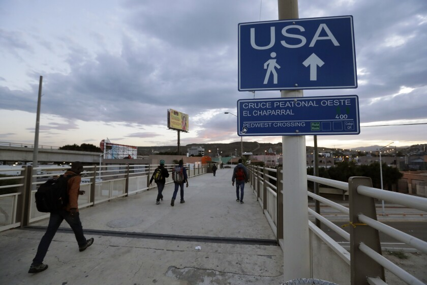 FILE - In this Sept. 27, 2016 file photo, Haitians make their way towards the border crossing in Tijuana, Mexico. The Trump administration is planning to expand the collection of DNA from migrants who cross the U.S. border, and to include the information in a massive criminal database operated by the FBI (AP Photo/Gregory Bull, file)