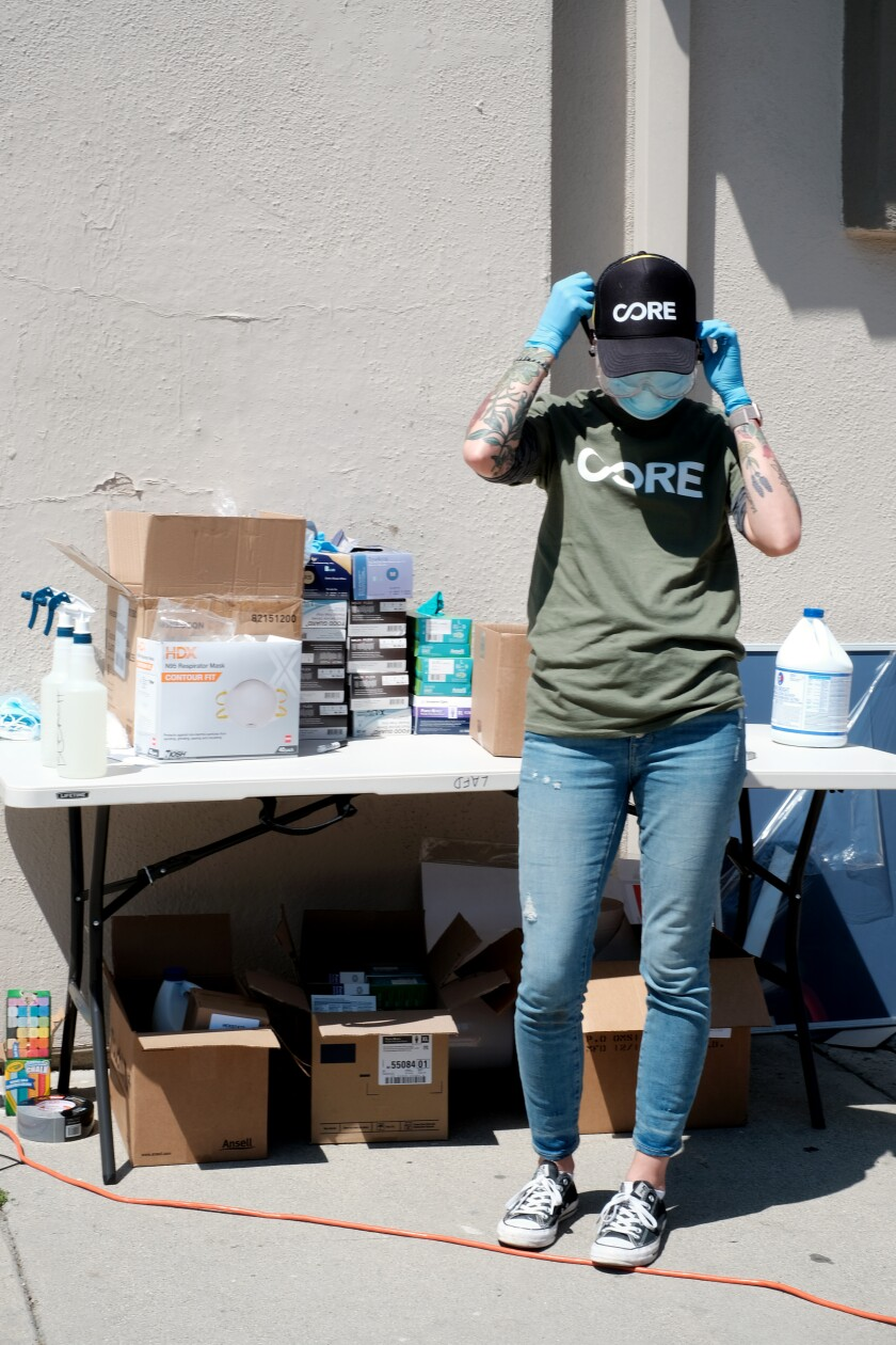 A Community Organized Relief Effort, or CORE, worker prepares to staff a COVID-19 drive-thru facility earlier this week in East Los Angeles