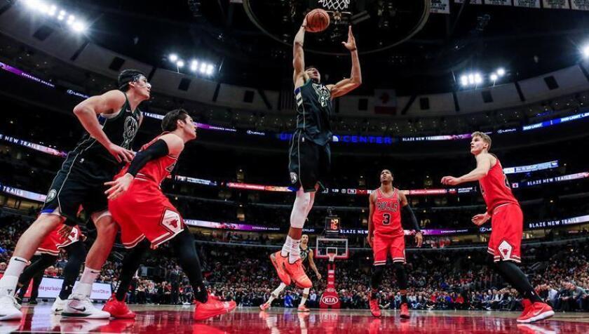 El alero griego Giannis Antetokounmpo (c) de los Milwaukee Bucks lanza a canasta este lunes en el partido que su equipo ha disputado ante los Chicago Bulls en el United Center de Chicago, Illinois (EE. UU.). EFE