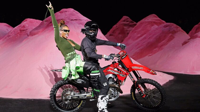 Rihanna takes her runway finale bow on the back of a motocross bike after the show.