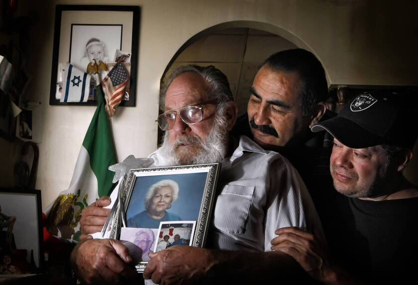 Eddie Goldstein in 2009 in the Boyle Heights home where he lived for six decades; he is holding a photograph of his late wife, Esther. With him are his sons Arthur Perez and Steven Goldstein.