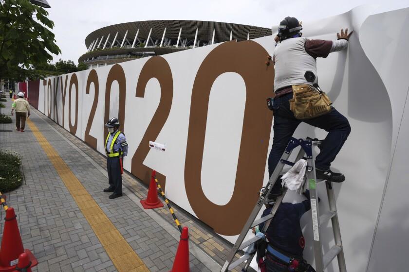 Obreros colocan logos en una barrera frente al Estadio Nacional, sede de la ceremonia de apertura
