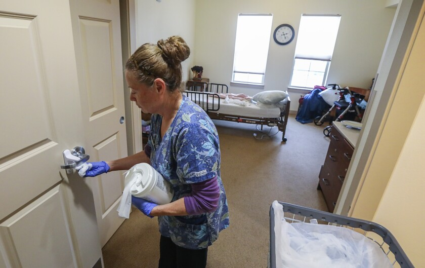 Mina Montano, an environmental aide at St. Paul's Plaza independent and assisted living facility, uses disinfectant wipes to do more frequent cleaning of the high-touch areas of a resident's room in the Memory Care unit on Mar. 10.