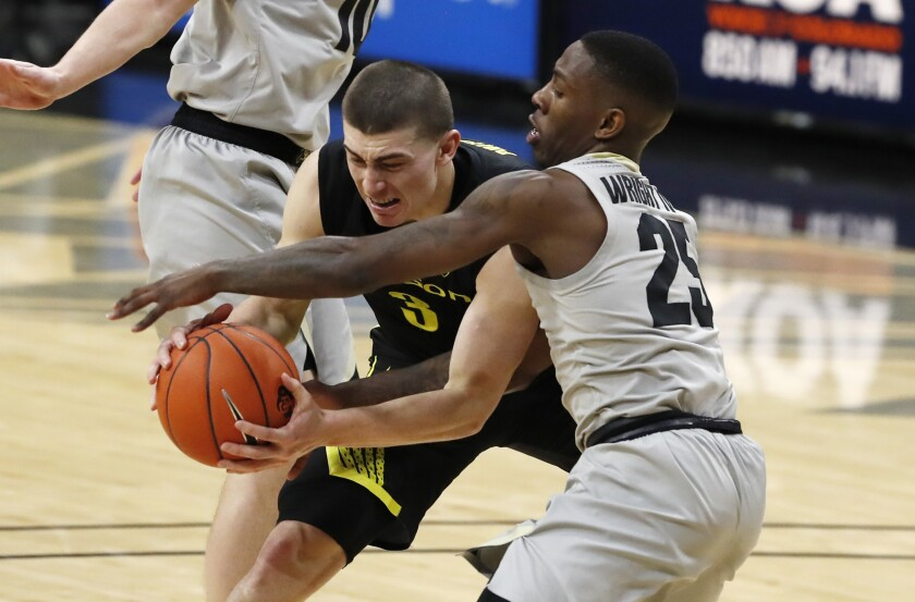 Oregon guard Payton Pritchard, left, fights for control of the ball with Colorado guard McKinley Wright IV in the first half of an NCAA college basketball game Thursday, Jan. 2, 2020, in Boulder, Colo. (AP Photo/David Zalubowski)