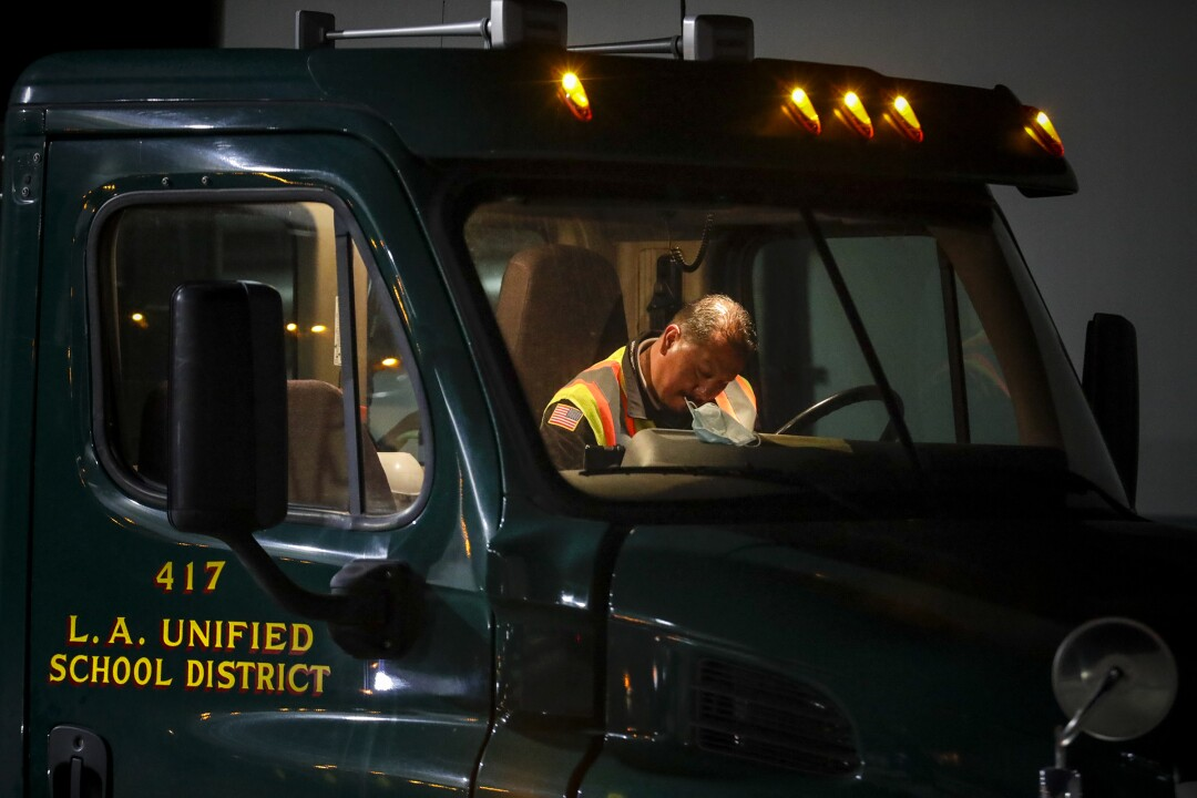 In the early morning darkness a truck driver goes over paperwork before going out delivering food from LAUSD Procurement Services Center in Pico Rivera.
