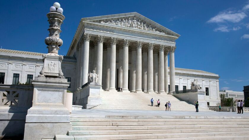 FILE - In this April 26, 2014 file photo, people walk on the steps of the U.S. Supreme Court in Wash