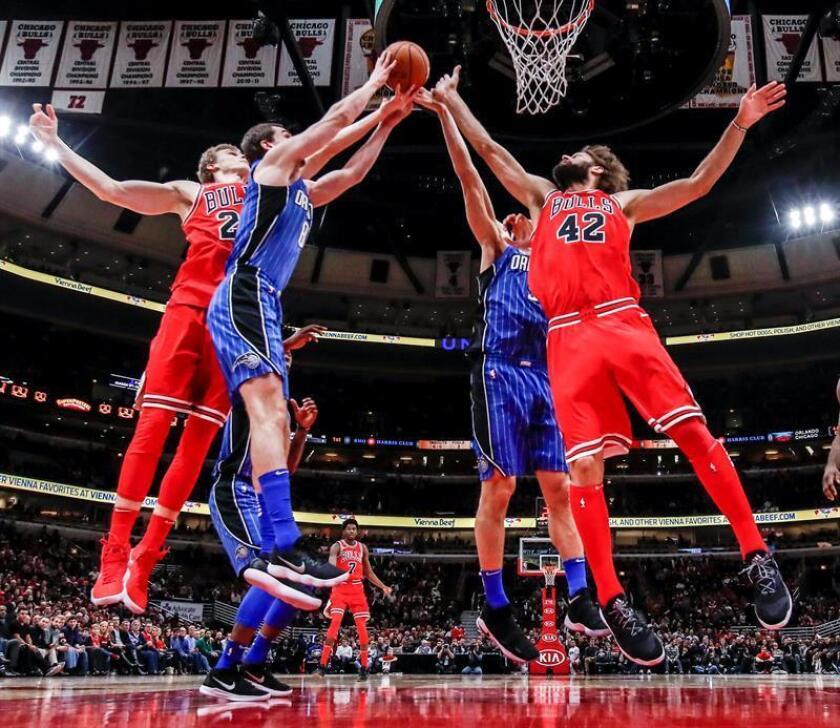 Robin Lopez (d) y Lauri Markkanen (i) de Chicago Bulls en acción ante Nikola Vucevic (2-d) y Mario Hezonja (2-i) de Orlando Magic durante un juego de la NBA entre Orlando Magic y Chicago Bulls en United Center en Chicago (EE.UU.). EFE