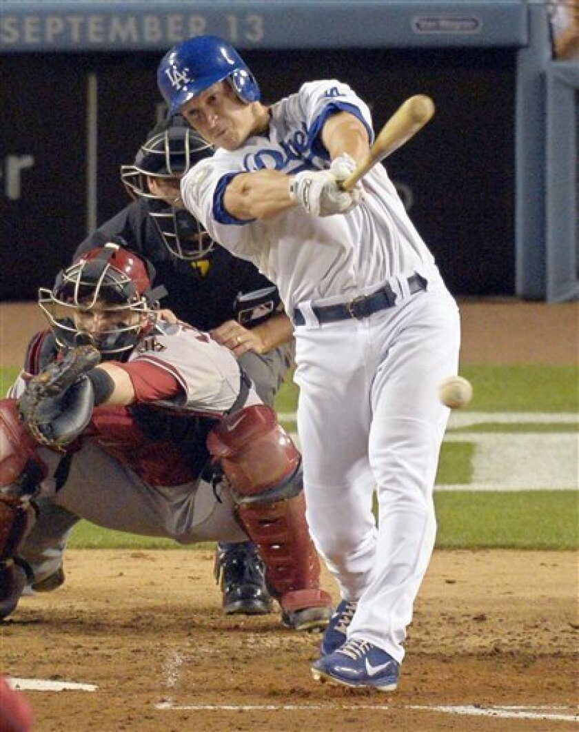 Los Angeles Dodgers' Mark Ellis, right, hits a two RBI single as Arizona Diamondbacks catcher Miguel Montero catches during the fifth inning of their baseball game, Friday, Aug. 31, 2012, in Los Angeles. (AP Photo/Mark J. Terrill)
