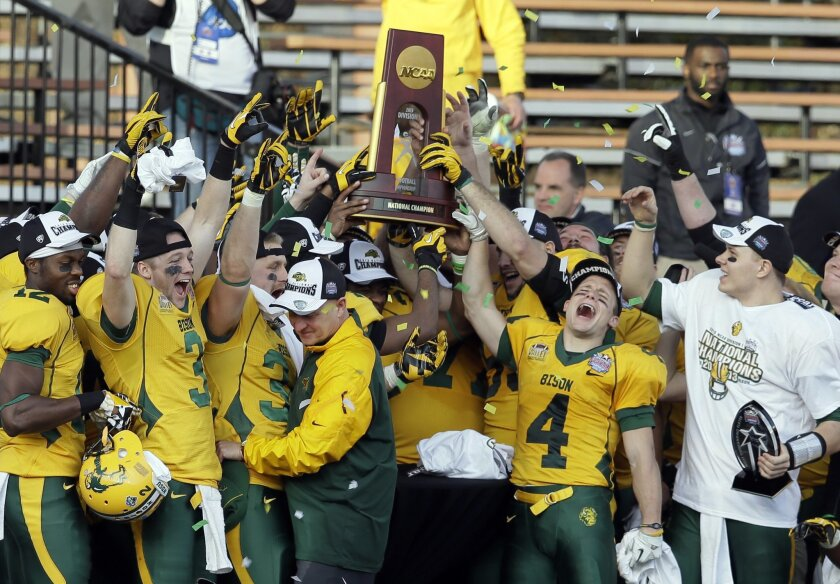 North Dakota State players celebrate with the trophy after winning the FCS championship NCAA college football game against Towson, Saturday, Jan. 4, 2014, in Frisco, Texas. NDSU won 35-7. (AP Photo/Tony Gutierrez)