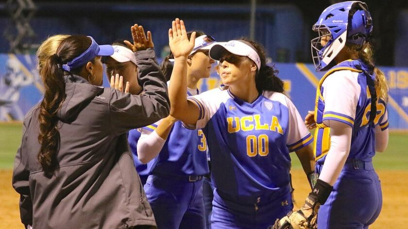 Pitcher Rachel Garcia high-fives UCLA coach Kelly Inouye-Perez after the final out of Sunday night's