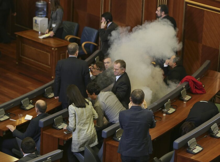 Opposition lawmakers release a tear gas canister disrupting a parliamentary session in Kosovo capital Pristina on Friday Feb. 19, 2016. Kosovo opposition again has used tear gas inside the Parliament disrupting its session, a repeated use of violent methods over the last five months to convince the government renounces its deals with Serbia and Montenegro. The opposition coalition has given the government an ultimatum until Feb. 27, to resign and call new elections in Kosovo. (AP Photo/Visar Kryeziu)