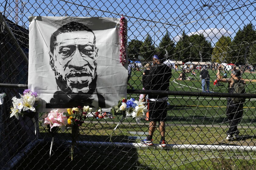 Flowers are placed next to an image of George Floyd on a fence surrounding Cal Anderson Park, Wednesday, June 17, 2020, inside what has been named the Capitol Hill Occupied Protest zone in Seattle. Police pulled back from several blocks of the city's Capitol Hill neighborhood near the Police Department's East Precinct building earlier in the month after clashes with people protesting the police killing of Floyd in Minneapolis. (AP Photo/Ted S. Warren)