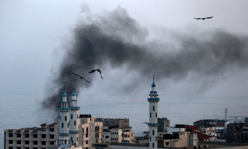 Smoke rises from a building in Gaza City after Israeli airstrikes Nov. 13.