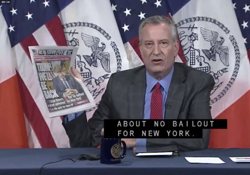 New York City Mayor Bill de Blasio, at his news briefing on Tuesday, holds up a copy of the New York Post featuring President Trump.