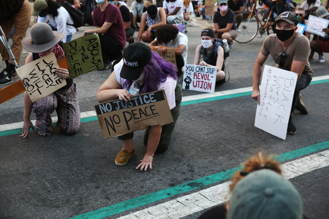 During a Black Lives Matter Los Angeles and Build Build meeting in downtown LA, people take one knee to touch the ground.