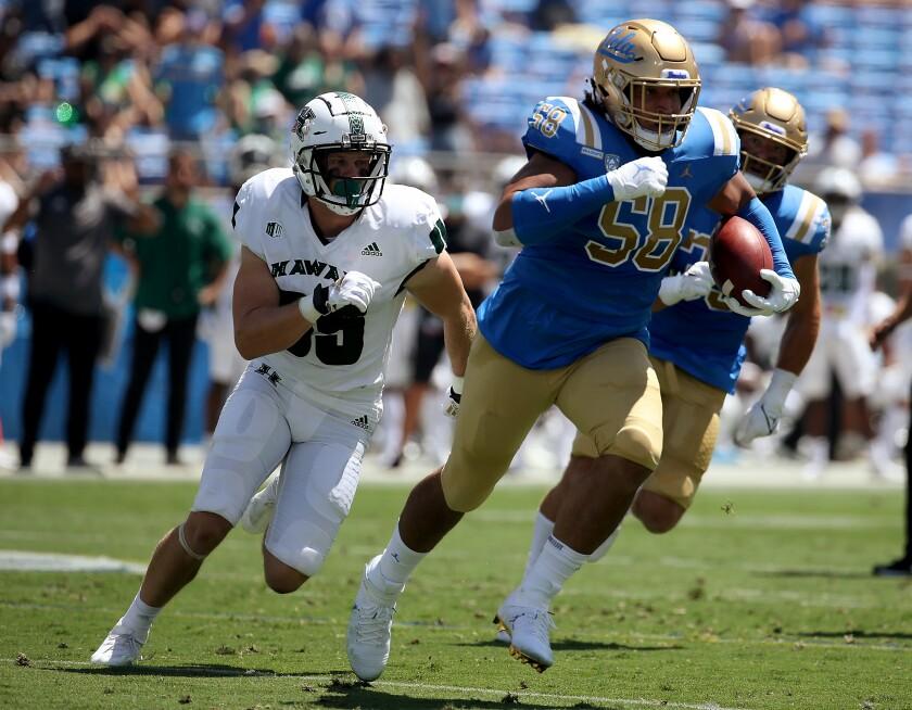 UCLA defensive lineman Datona Jackson returns an interception during the first quarter.