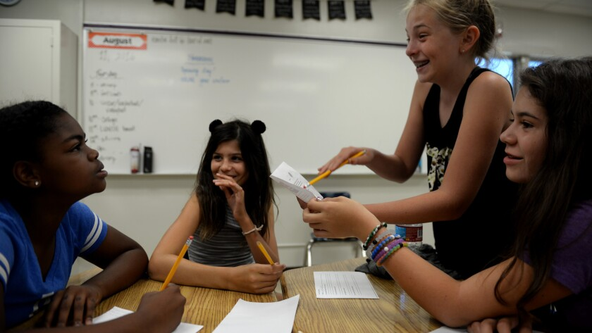 Students giggle during a light moment while attending a forensics workshop during the Girls Academic Leadership Academy orientation in Los Angeles.