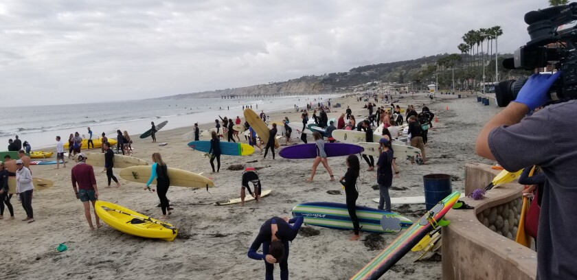 People head out on surfboards, paddleboards and kayaks in a protest paddle-out organized by Groundswell Community Project.