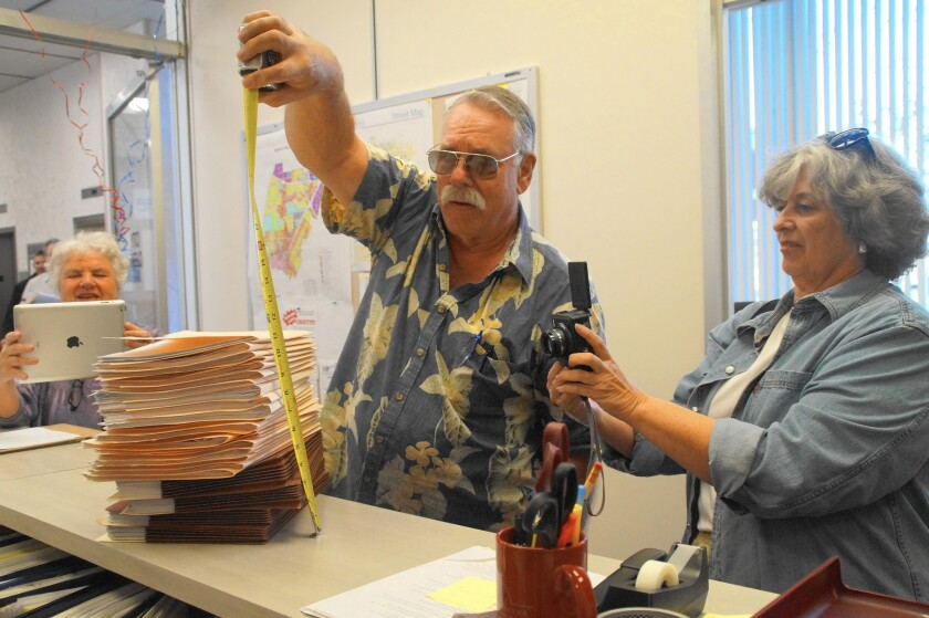 Jay Humphrey of Costa Mesa First measures the height of petition paperwork that he and others presented to the Costa Mesa city clerk's office on Jan. 4as Mary Spadoni, left, and Sally Humphrey take photos.