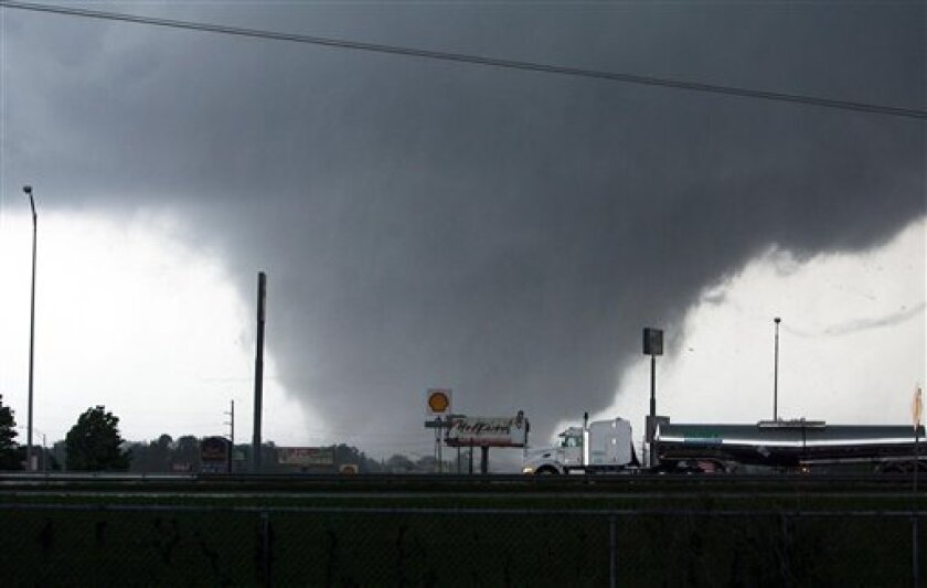 A tornado moves through Tuscaloosa, Ala. Wednesday, April 27, 2011. A wave of severe storms laced with tornadoes strafed the South on Wednesday, killing at least 16 people around the region and splintering buildings across swaths of an Alabama university town. (AP Photo/The Tuscaloosa News, Dusty C