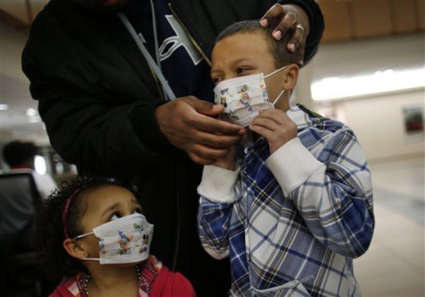Damien Dancy puts masks on his children Damaya, 3, left, and Damien, 7, on Wednesday, Jan. 9, 2013 at Sentara Princess Anne Hospital in Virginia Beach, Va. Hospitals in Hampton Roads are urging patients and visitors to wear a mask at their facilities to help stop the spread of the flu. The recommendation was issued Wednesday by more than two dozen medical centers. In a joint statement, the hospitals said the recommendation applies to hospitals, urgent care centers and branch clinics, among others. (AP Photo/The Virginian-Pilot, Stephen M. Katz)