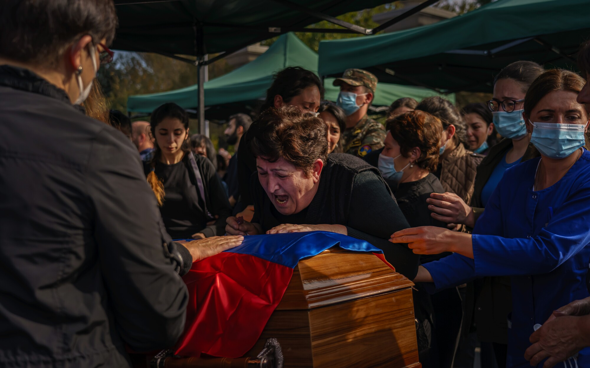 A woman wails over a casket at the funerals of Kristapor Artin and Suren Vanyan, volunteer fighters for Armenia.