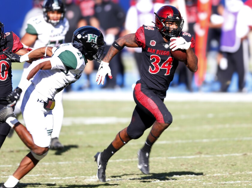 San Diego State's Greg Bell runs past Hawaii's Micheal Washington in the first quarter for a 62-yard touchdown.