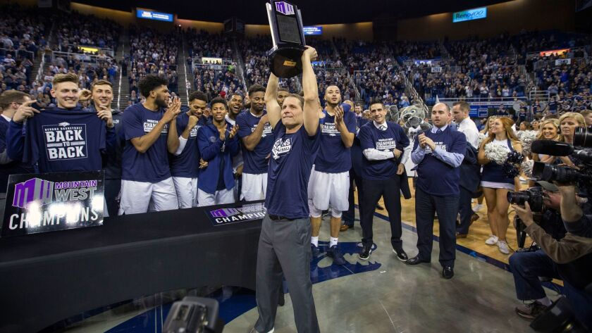 Nevada head coach Eric Musselman, center, holds up the trophy after his team's victory over Colorado