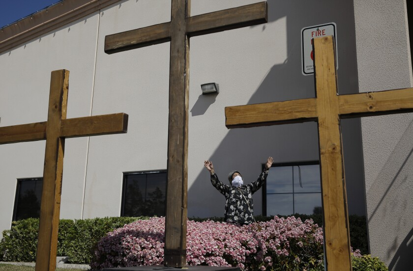 File - In this April 12, 2020, file photo, Norma Urrabazo prays while wearing a face mask before speaking at an Easter drive-in service at the International Church of Las Vegas, in Las Vegas. A rural Nevada church is asking a U.S. appeals court to overturn a federal judge's refusal to strike down the state's 50-person cap on religious gatherings as unconstitutional. Calvary Chapel Dayton Valley filed formal notice of its appeal to the 9th U.S. Circuit Court of Appeals in San Francisco after a judge in Las Vegas rejected its second request last week for a preliminary injunction blocking enforcement of the flat cap. (AP Photo/John Locher, File)