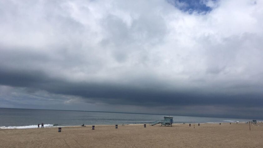 Storm clouds hang low over Manhattan Beach as an unusual late-season weather system brought rain and below-normal temperatures to the Los Angeles region.