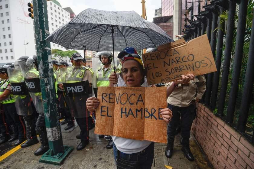 Una mujer pide que se revoque el hambre, un paralelismo al proceso de destitución que promueve la oposición y la lucha contra el hambre de los venezolanos debido a la crisis económica, durante una manifestación realizada en julio de 2016 en Caracas.