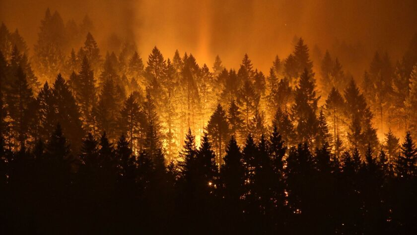 A wildfire continues to burn on the Oregon side of the Columbia River Gorge near Cascade Locks, Ore.