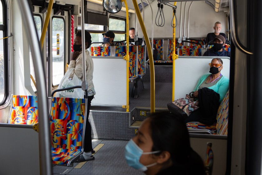 Bus riders in Los Angeles wear masks and sit far apart from one another.