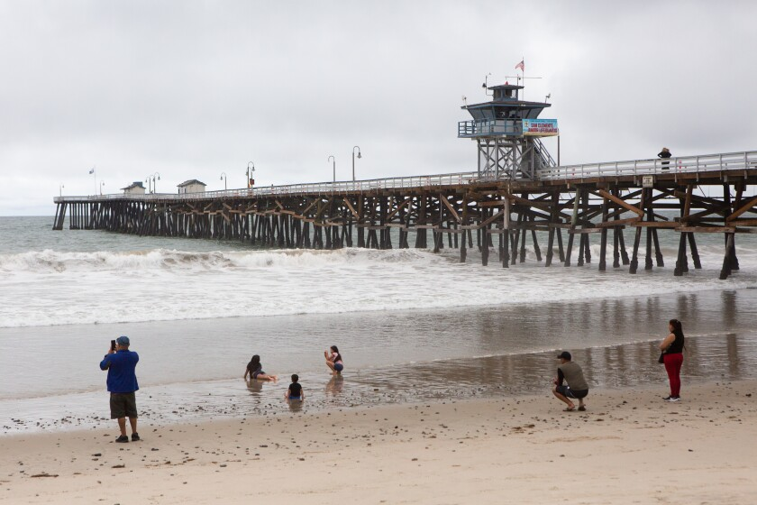 Families practice social distancing while playing in the water and sand near the San Clemente Pier on May 18.