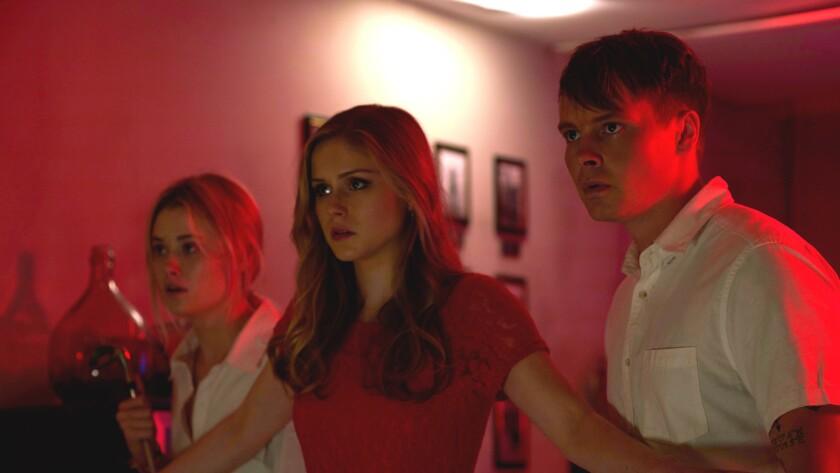 (L-R) Virginia Gardner as Iris, Erin Moriarty as Alexis, and Sam Strike as Casper in the horror/thri