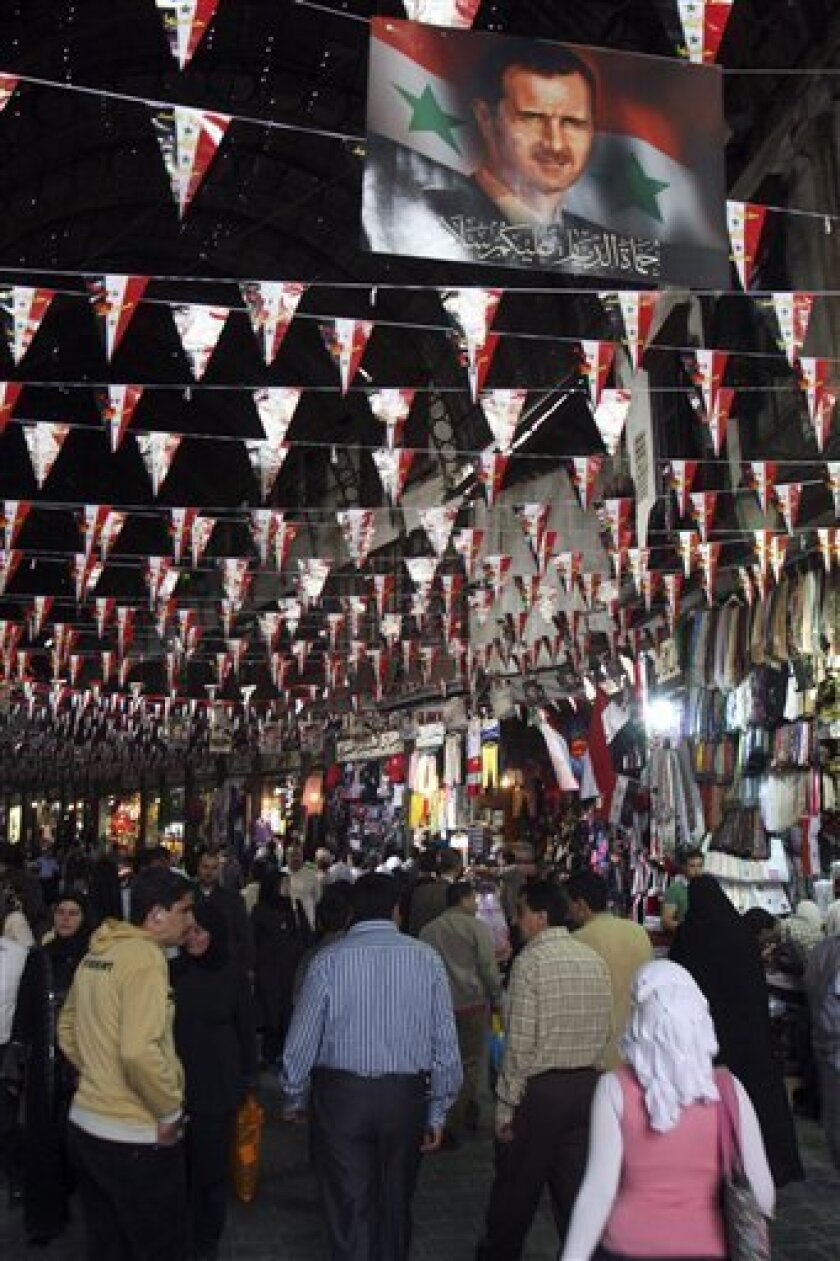 People walk at Hamidiyah market in the old city of Damascus, Syria, Sunday, April 3, 2011. Syrian President Bashar Assad appointed a former agriculture minister Sunday to form a new government, part of a series of overtures toward reform as the country faces a wave of anti-government protests.(AP Photo/ Bassem Tellawi)