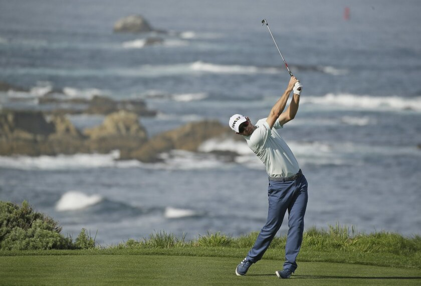 Justin Rose follows his shot from the fourth tee of the Spyglass Hill Golf Course during the first round of the AT&T Pebble Beach National Pro-Am golf tournament Thursday, Feb. 11, 2016, in Pebble Beach, Calif. (AP Photo/Eric Risberg)
